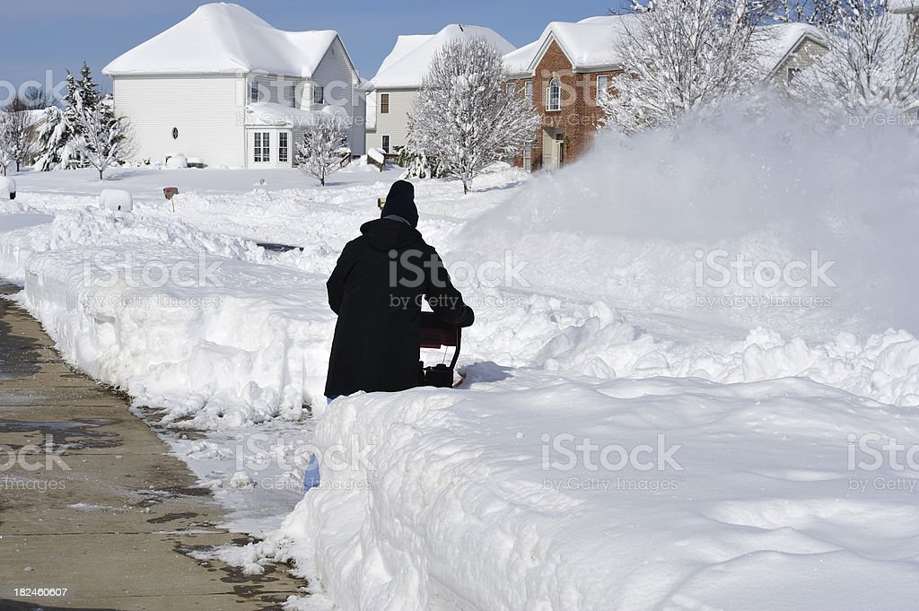 Man using Snowblower to remove Blizzard Snow royalty-free stock photo