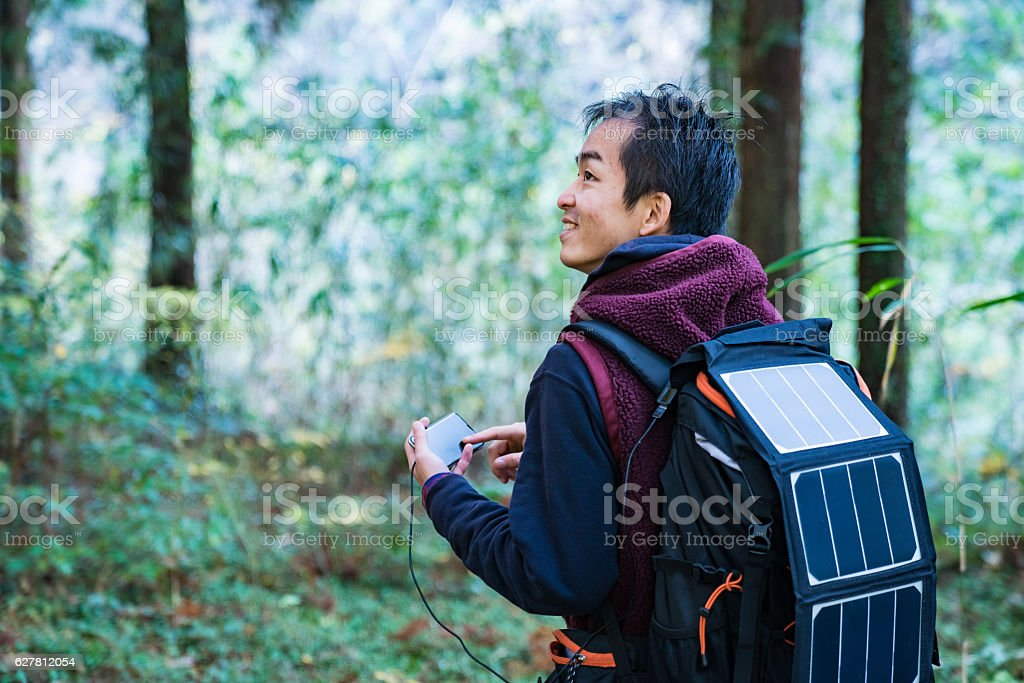 Man using solar cells to power smartphone in the forest stock photo