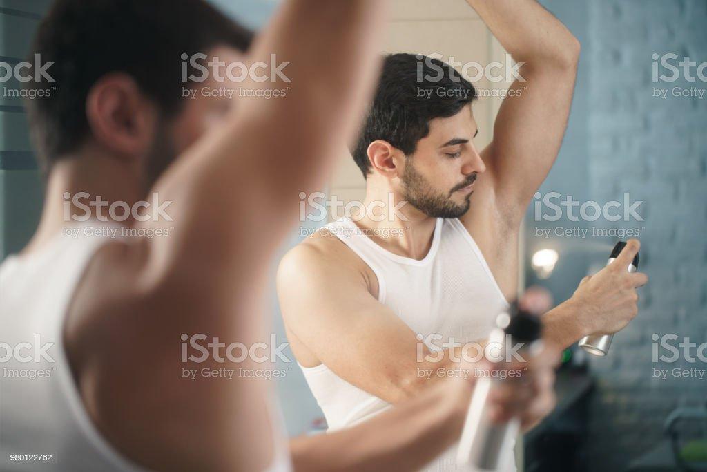 Man Using Spray Deodorant On Underarm For Bad Smell stock photo