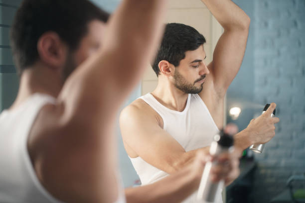 Man Using Spray Deodorant On Underarm For Bad Smell stock photo