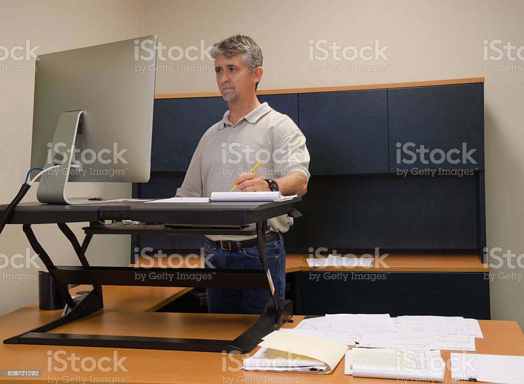 Man using stand up desk in office for good health A man is working at a standup desk in an office where he works because standing is healthier than sitting all day. Live healthy, don't sit all day. Adjustable Stock Photo