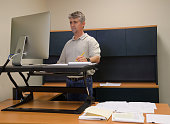 Man using stand up desk in office for good health