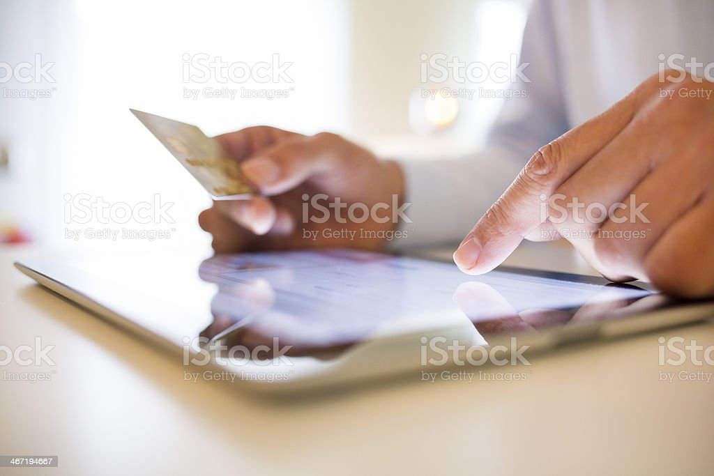Man using tablet and holding credit card stock photo