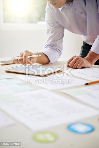 Crop man with pen and papers on table using tablet while creating modern interface design