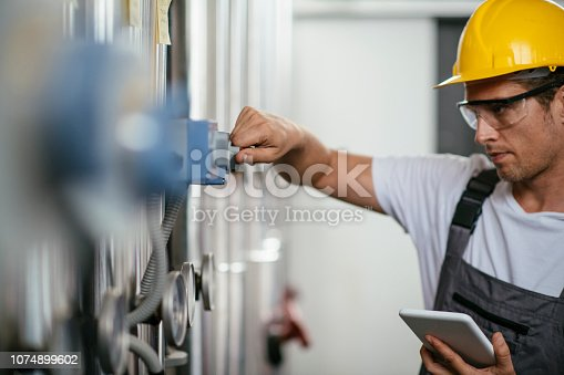 Man using tablet at Natural gas processing facility. Shadow DOF. Developed from RAW; retouched with special care and attention; Small amount of grain added for best final impression. 16 bit Adobe RGB color profile.