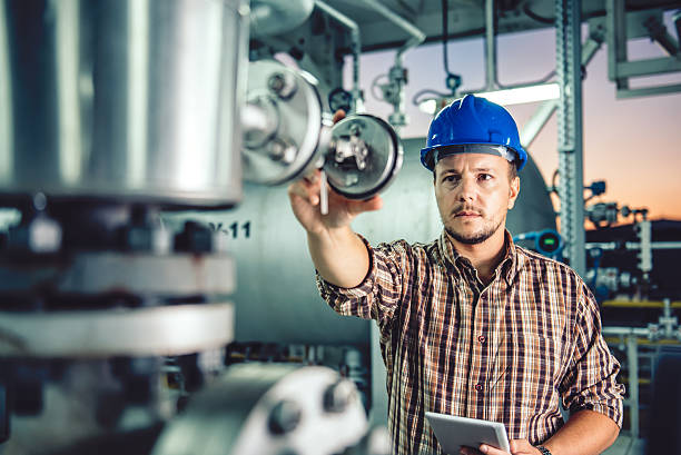 Man using tablet at Natural gas processing facility Man wearing blue hardhat using tablet at Natural gas processing facility chemical plant stock pictures, royalty-free photos & images