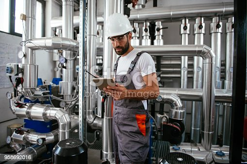 Man using tablet at Natural gas processing facility. Shallow DOF. Developed from RAW; retouched with special care and attention; Small amount of grain added for best final impression. 16 bit Adobe RGB color profile.