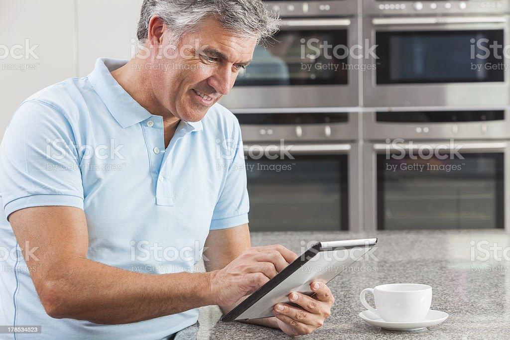 Man Using Tablet Computer in Kitchen Drinking Coffee royalty-free stock photo