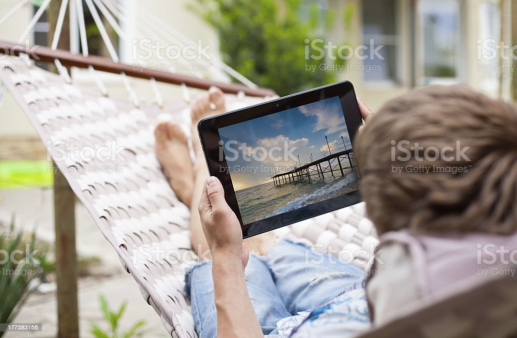 Man using  tablet computer while relaxing in a hammock stock photo