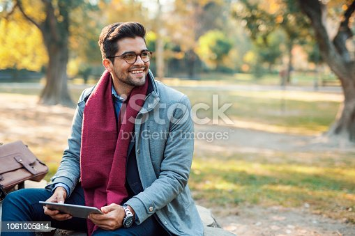 Handsome young businessman reading at public park