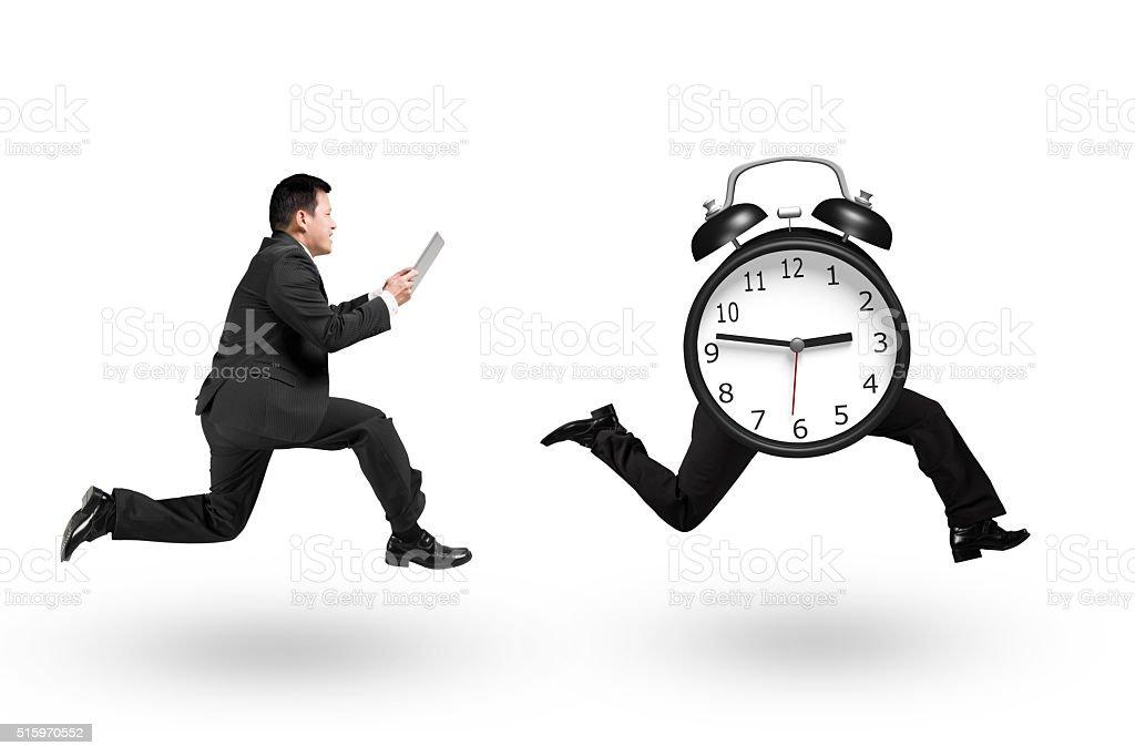 Man using tablet running after alarm clock of running legs stock photo