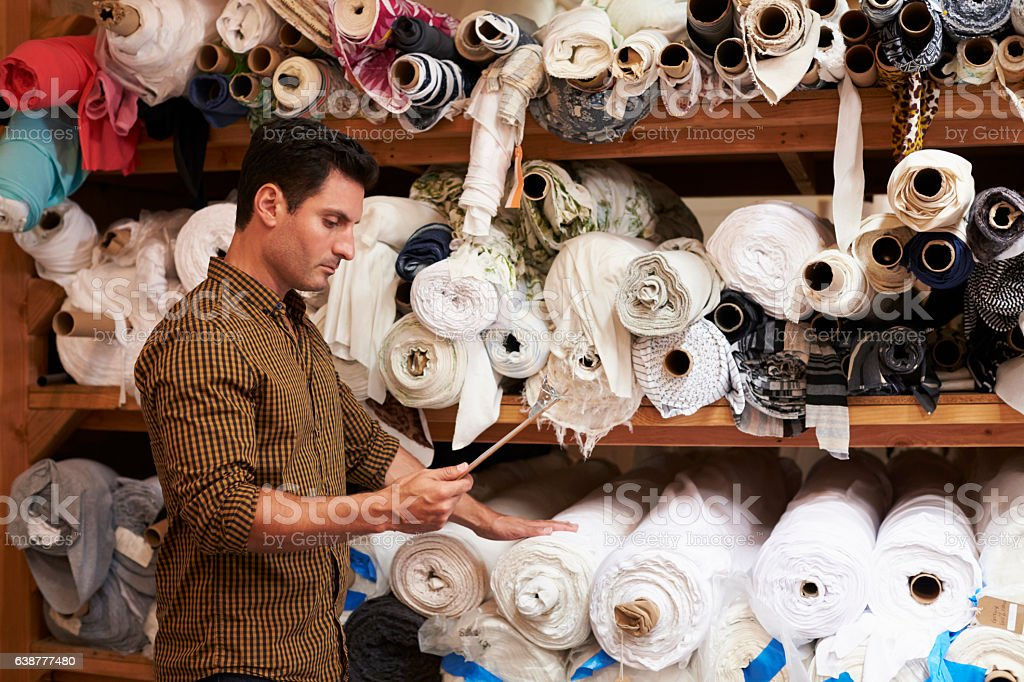 Man using tablet selects fabric from storage shelves stock photo