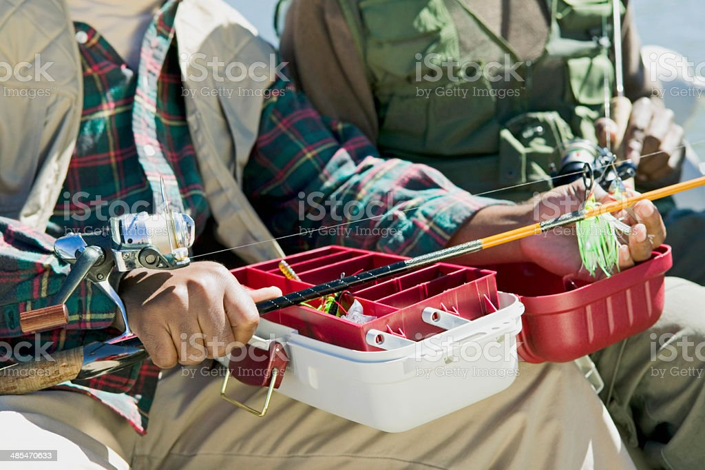 Man Using Tackle Box and Preparing Fishing Pole stock photo