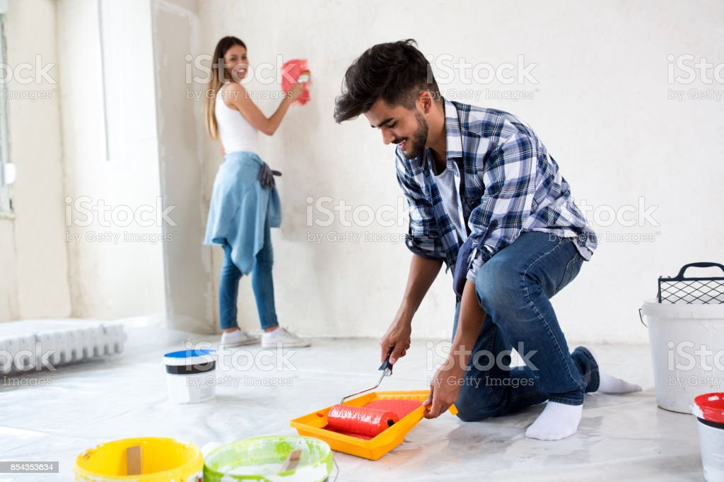 Man Using Take Color With Roller To Painting House Stock