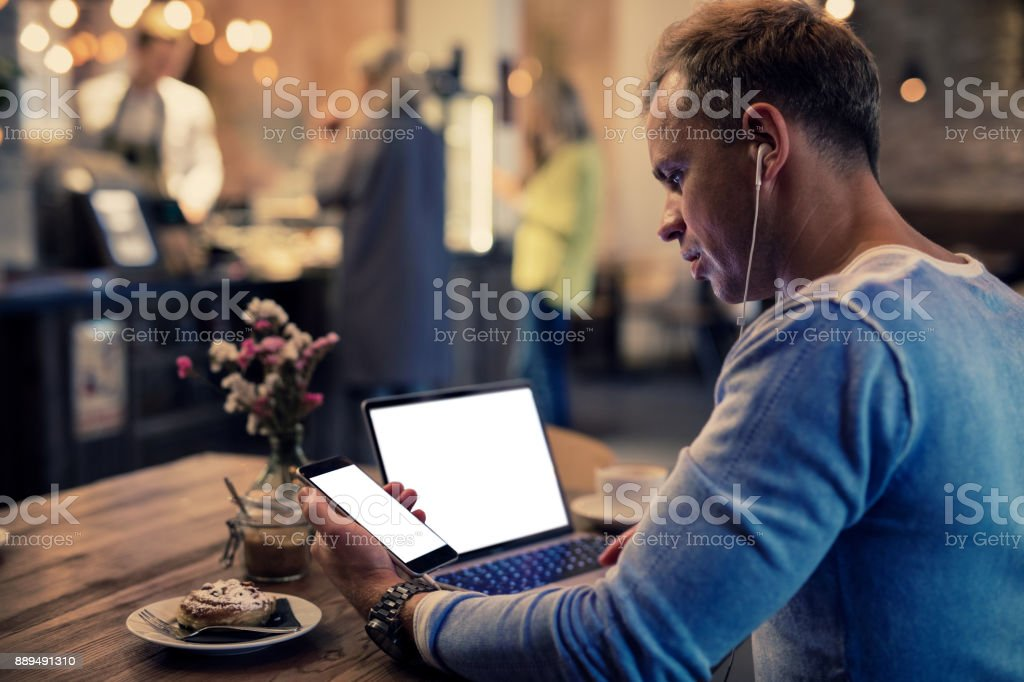Man using tech devices in cafe. stock photo