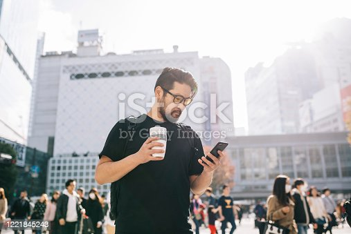 Asian man using a smartphone to check for directions and drinking coffee from a reusable cup