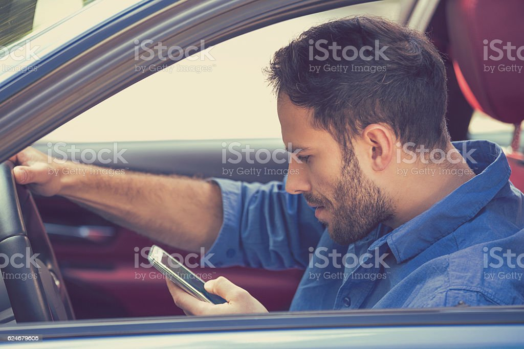 man using texting on mobile phone while driving a car stock photo