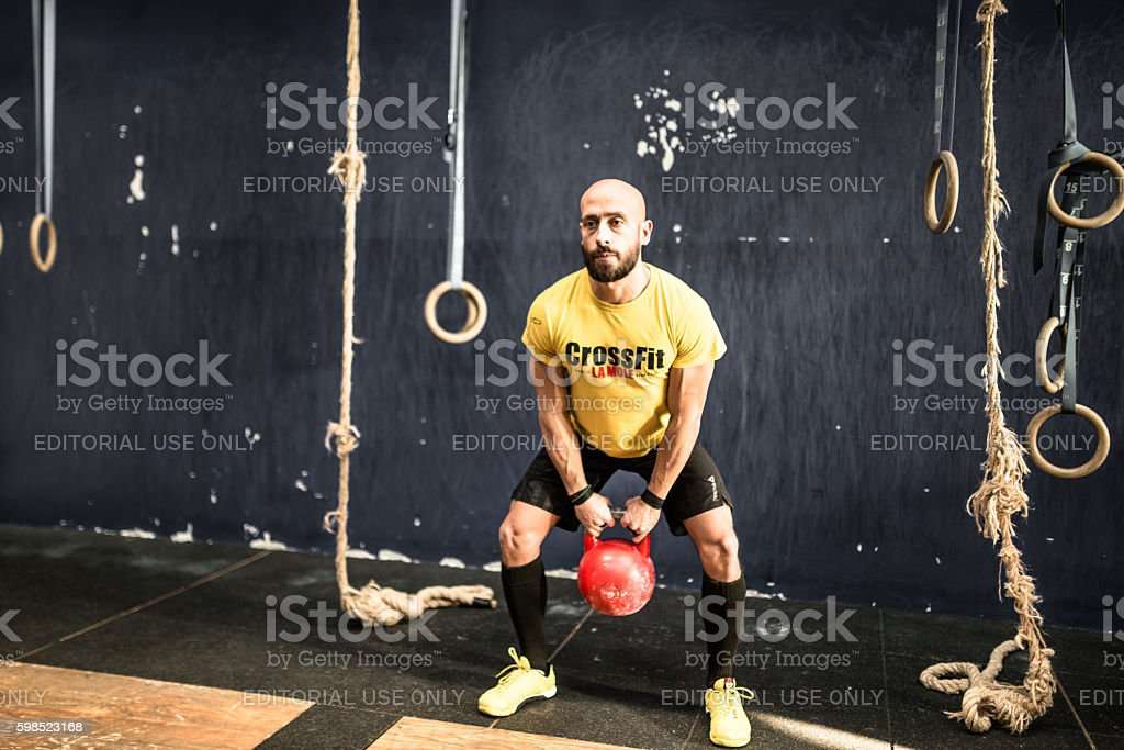 man using the kettlebell on the gym stock photo