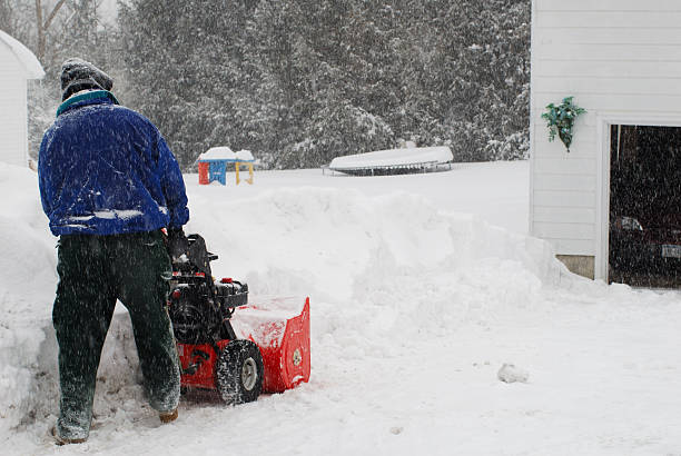 man using the snowblower in a snowstorm stock photo