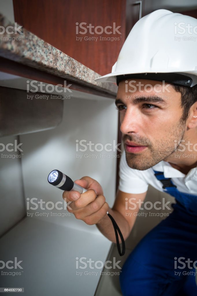 Man using torch while kneeling y sink royalty-free stock photo