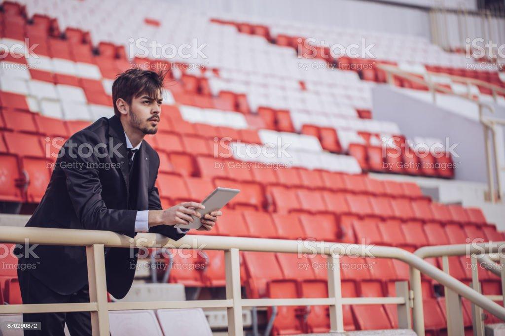 Man using touchpad on stadium stock photo