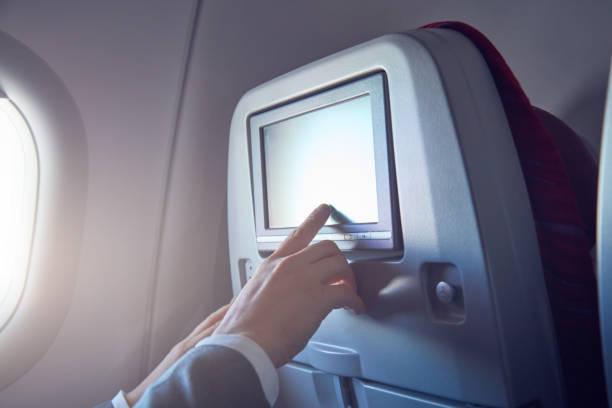 Mann mit Touchscreen in modernen Flugzeugsitz. – Foto