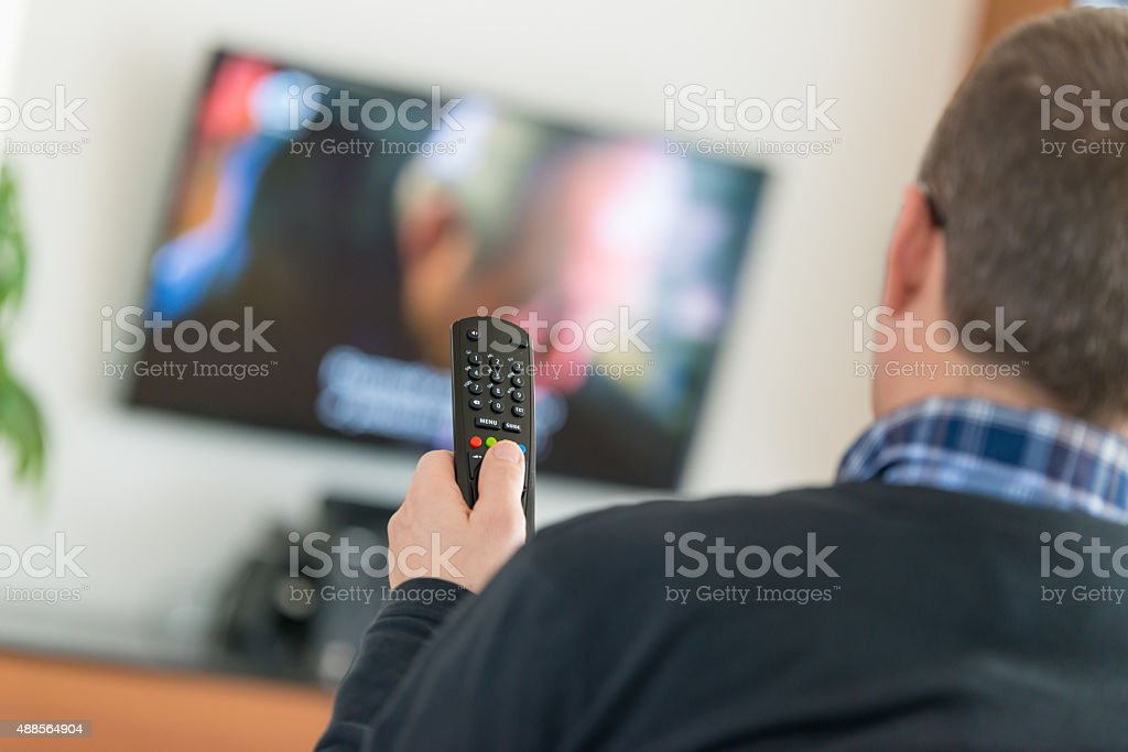 Man using TV Remote Control stock photo