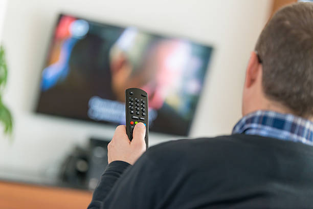 Man using TV Remote Control Man holding a Television remote control, changing channels, selective focus on the foreground with TV on in the background. cable tv stock pictures, royalty-free photos & images