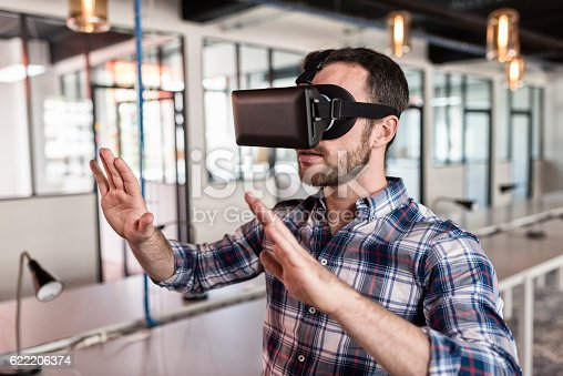 istock Man using virtual reality glasses in startup office. 622206374