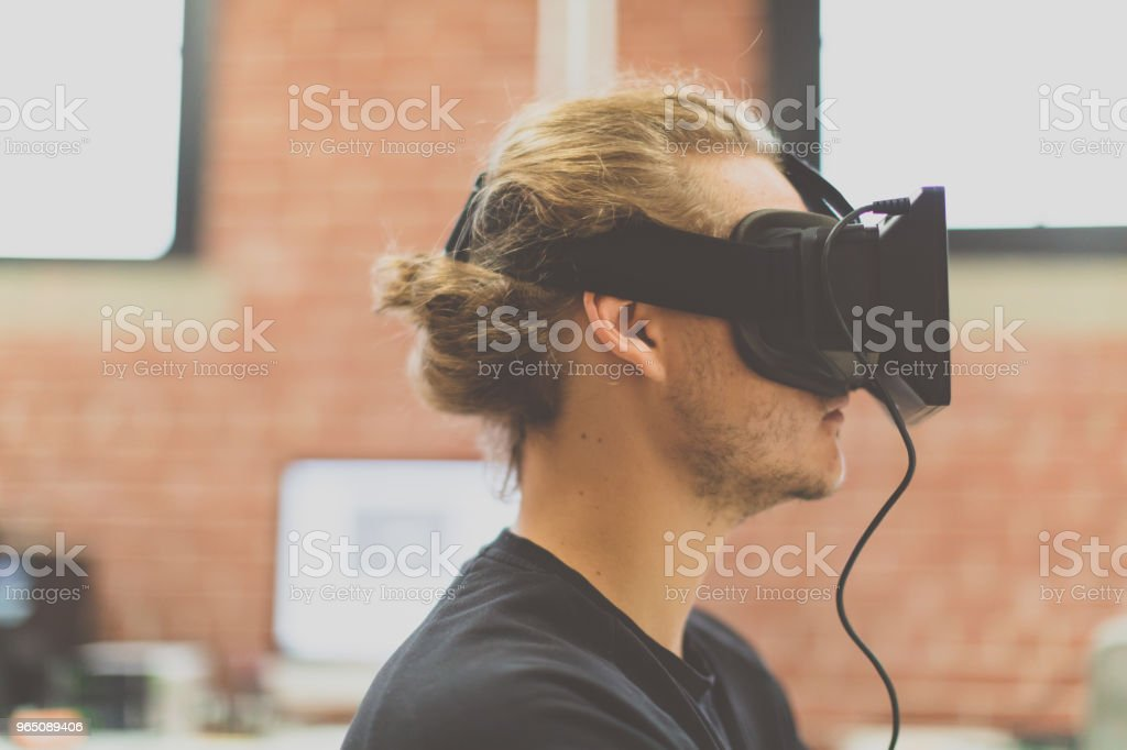 Man using virtual reality headset in a woking place. Augmented reality royalty-free stock photo