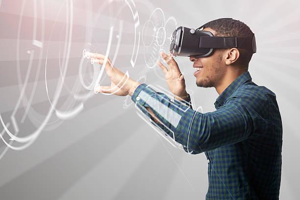 Man Using Virtual Reality Headset Man Using Virtual Reality Headset emergence stock pictures, royalty-free photos & images