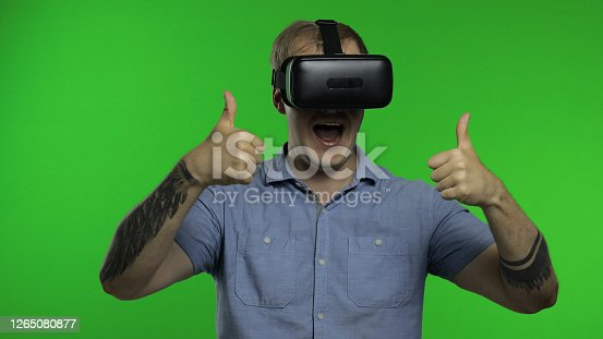 Young hansome man using VR headset helmet to play game. Watching virtual reality 3d 360 video. Isolated on chroma key green background in studio. Future technology. Guy in VR goggles looking around