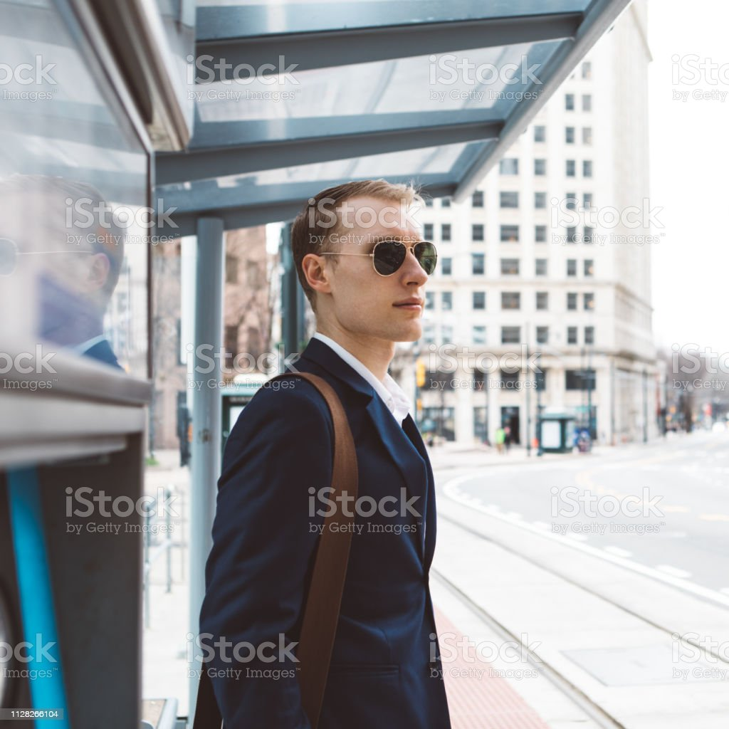 man using waiting at the bus stop stock photo