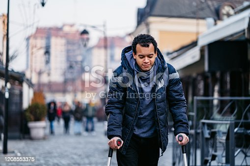 Young mixed raced injured man using walking canes for walking downtown.