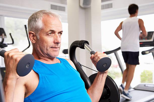 Hombre usando la máquina de ejercicios con pesas con corredor en la máquina trotadora en el fondo - foto de stock