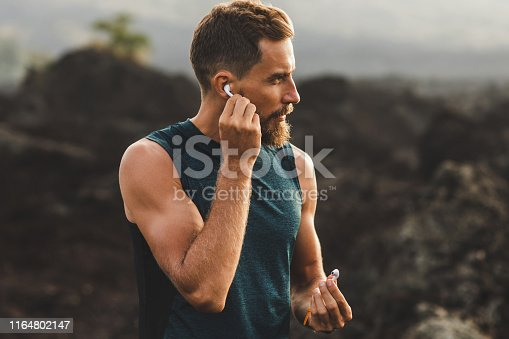 istock Man using wireless earphones air pods on running outdoors. Active lifestyle concept. 1164802147
