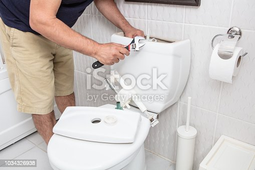Man using wrench repairing toilet cistern in a concept of DIY repairs with copy space