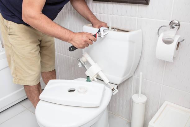 トイレの貯水槽の修理レンチを使用して男 - お手洗い ストックフォトと画像