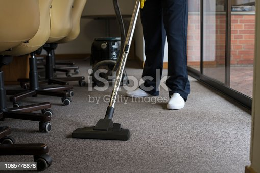 Man cleaning a rug with a vacuum cleaner, in an office, with his uniform, smiling, happy with his work