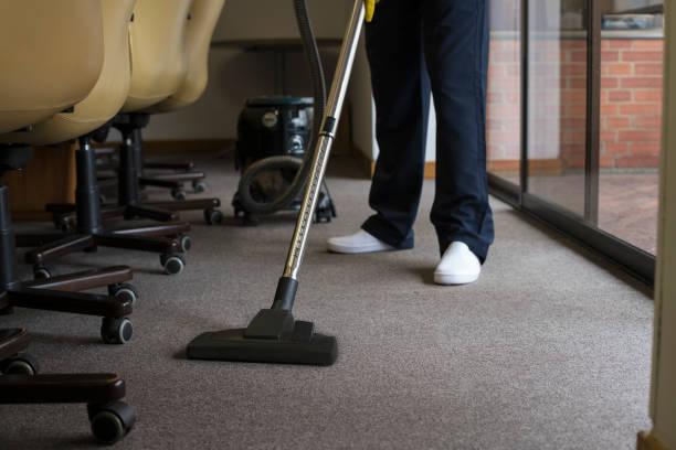 man vacuuming the carpet of an office - cleaning zdjęcia i obrazy z banku zdjęć