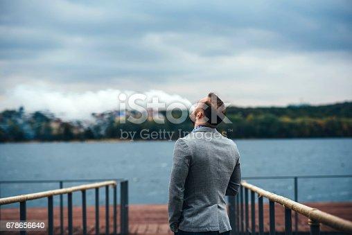 istock Man vape electronic cigarette outdoor 678656640