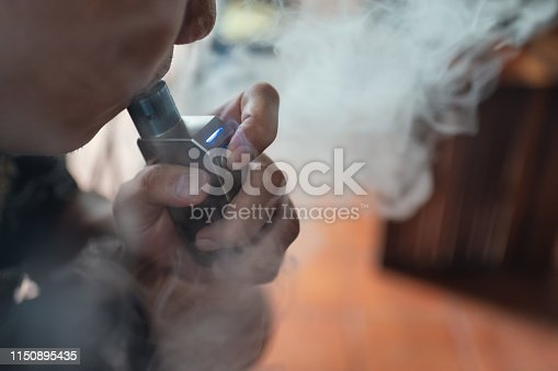 istock Man vaping of electric cigarette with vapor 1150895435
