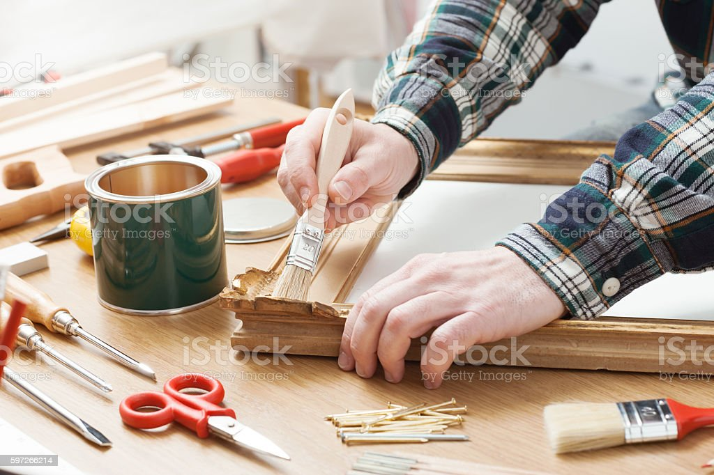 Man varnishing a wooden frame at home royalty-free stock photo
