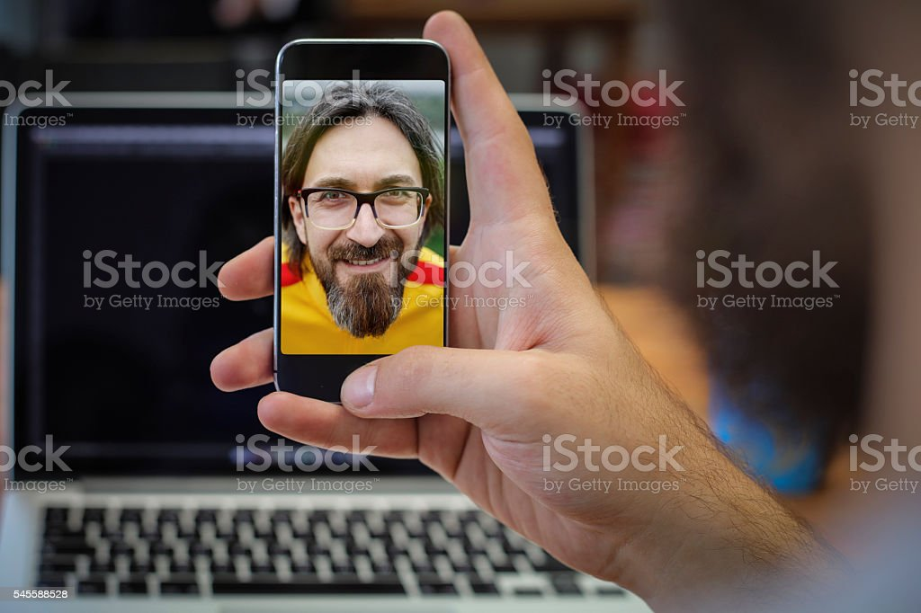 Man video conferencing on smartphone stock photo