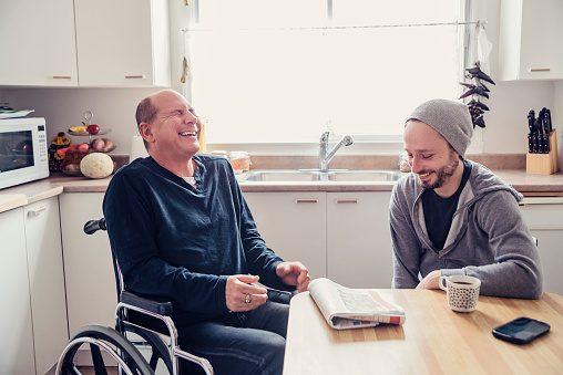 When a friend is hurt and in a temporary wheelchair, it is time to visit and change is mind. Two man having a chat and a coffee in a home kitchen, talking about the morning paper. Horizontal waist up indoors shot in natural light. This was shot in Montreal, Canada.