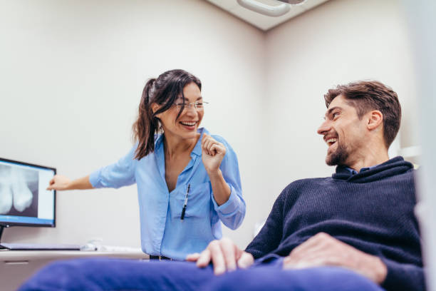 Man visiting female dentist at clinic stock photo