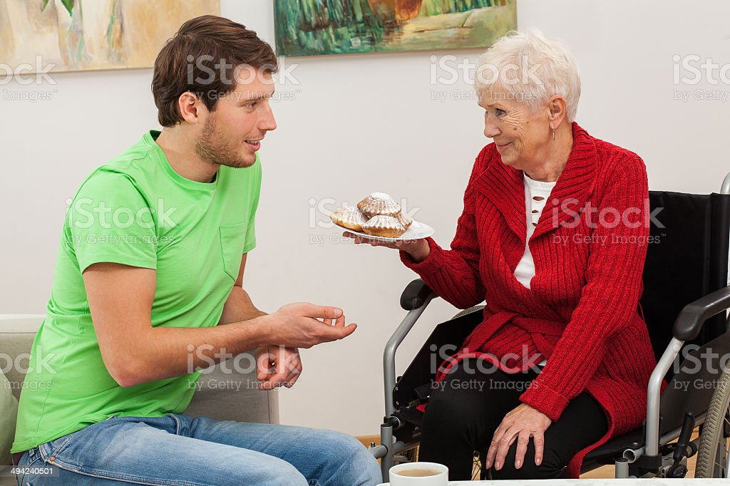 Man visiting his disabled aunt stock photo
