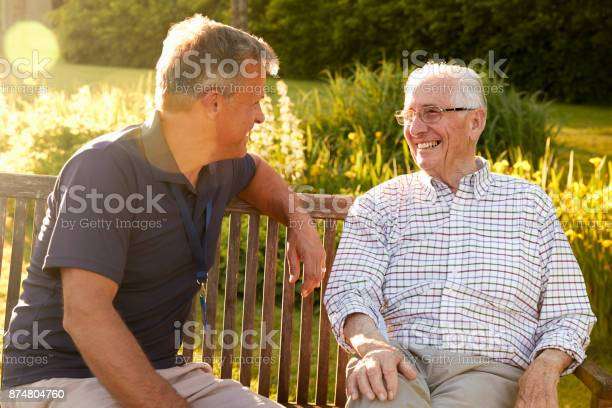 Mann Besuchen Senior Männlichen Verwandten In Einrichtung Für Betreutes Wohnen Stockfoto und mehr Bilder von 80-89 Jahre