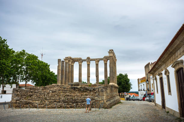 Man visiting the famous Roman Temple of Evora in Portugal\ stock photo