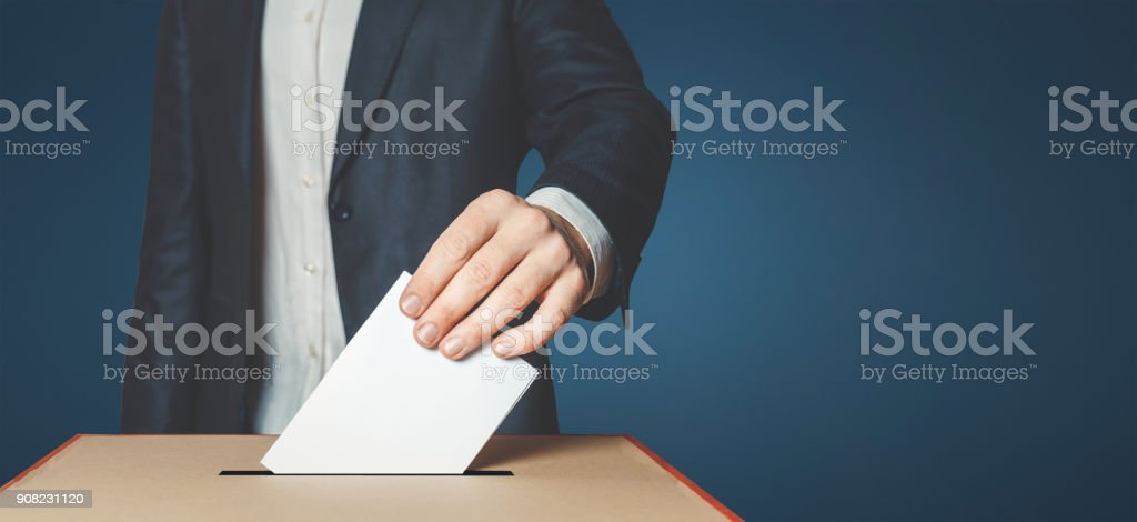 Man Voiter Putting Ballot Into Voting box. Democracy Freedom Concept stock photo